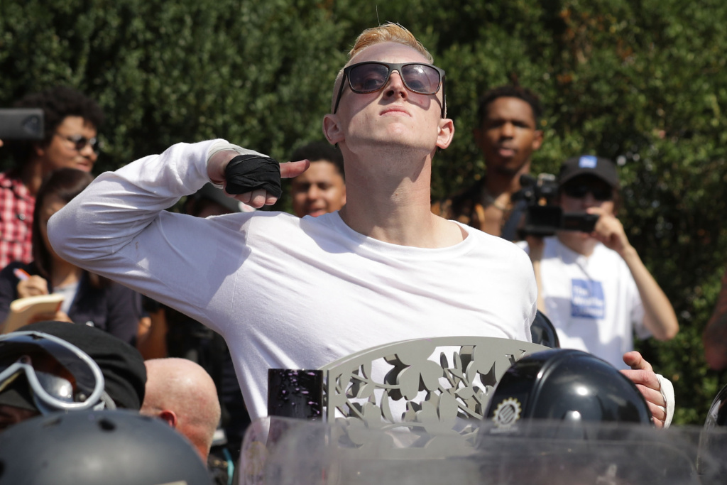 A man marching with white nationalists makes a slashing motion across his throat toward counter-protester in Charlottesville's white pride rally. (Chip Somodevilla/Getty Images)