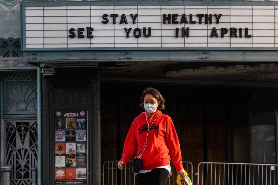 A woman walks wearing a mask to protect herself from the novel coronavirus (COVID-19) in front of a closed theater in Koreatown, Los Angeles, on March 21, 2020. (AFP, GETTY IMAGES)